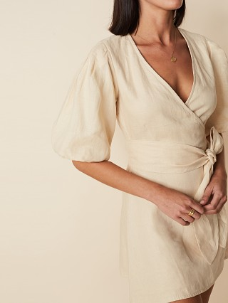 Model in plain sand Faithfull the Brand Godiva Wrap Dress