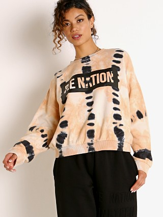 Model in coral gold tie dye PE NATION Score Runner Sweatshirt