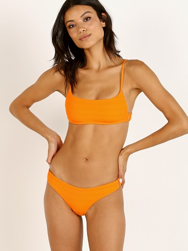 Model in tangerine L Space Piper Bikini Top