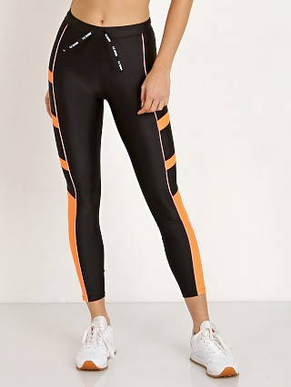 Model in black/orange PE NATION The Combination Legging