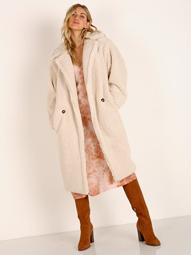 Model in ivory APPARIS Daryna Faux Shearling Double Breasted Coat Camel