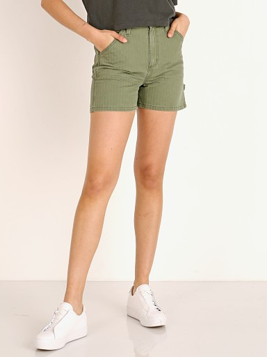 Model in vintage olive herringbone Lee High Rise Dungaree Short