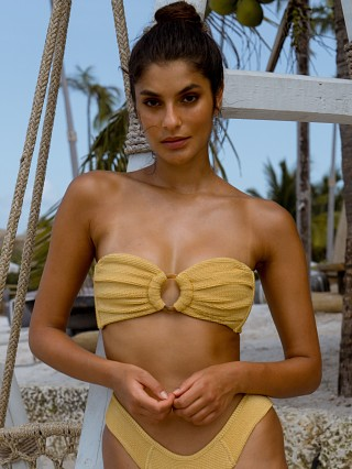 Model in goldie Montce Tori Bandeau Bikini Top