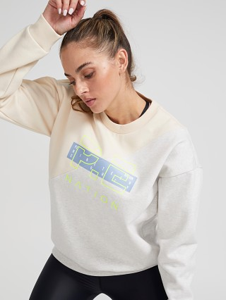 Model in pearled ivory grey PE NATION First Position Sweatshirt